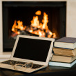 Laptop and pile of books against the background of the fireplace — Stok fotoğraf