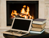 Laptop and pile of books against the background of the fireplace — Stockfoto