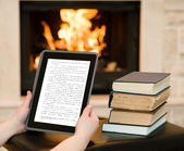Hands holding tablet computer near the fireplace — Stock Photo