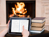 Person using digital tablet PC near the fireplace — Stock Photo