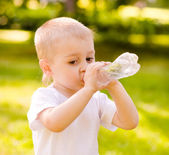 Little boy drinking fresh water in the park — Stock Photo