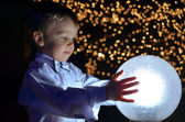 Boy holding a glowing ball. — Stock Photo