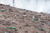Stack of different types garbage on the river bank — Stock Photo