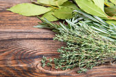 Fresh thyme, rosemary and laurel bay leaves bound on a wooden board — Stock Photo