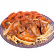 Stock Photo: Grilled chicken wings with French fries and onions rings
