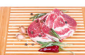 Raw meat, vegetables and spices on wooden board — Stock Photo