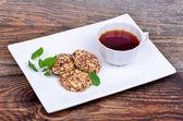 Biscoitos de cereais orgânicos em um prato e chá em fundo de madeira — Fotografia Stock