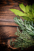 Fresh thyme, rosemary and laurel bay leaves bound on a wooden board — Stok fotoğraf
