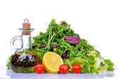 Salad mix with rucola, frisee, radicchio, lettuce and bottle of olive oil, lemon, tomatoes — Stock Photo