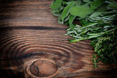 Fresh thyme, rosemary and sage leaves bound on a wooden board — Foto Stock