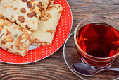 Pancakes and a cup of tea on wooden background — Stock Photo