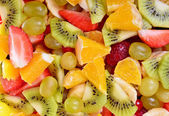 Top view of a fruit salad with strawberries, oranges, kiwi, blueberries and peaches — Stockfoto