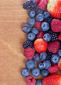 Different fresh berries as background. Top view — Stock fotografie