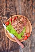 Bakade grishals, tomater, paprika, vitlök och kniv — Stockfoto