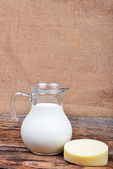 Glass jug with milk and piece of cheese — 图库照片