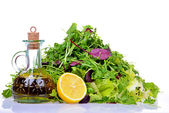 Salad mix with bottle of olive oil and lemon on white background — Stock Photo
