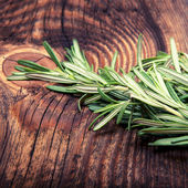 Fresh rosemary bound on a wooden board — Stock Photo
