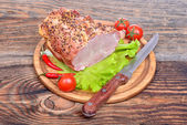 Baked pork neck, tomatoes, peppers, garlic and knife — Stock Photo