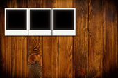 Photo frames on wooden board background texture — Stock Photo