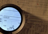 Gold index and magnifier — Stock Photo