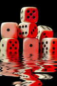 Sinking pile of red illuminated white dice — Stock Photo