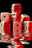 Sinking pile of red illuminated white dice — Stock Photo