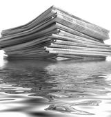 Sinking stack of newspapers — Stock Photo