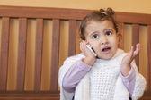 Little girl speak on the phone at home. — Stok fotoğraf