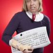 Woman holding a keyboard with carpal tunnel injury — Stockfoto