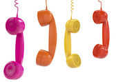 Hanging colored handsets — Stock Photo