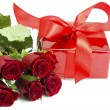 Bouquet of roses and red gift tied up by a bow — Stock Photo