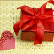 Gift and hearts on a wicker wood — Stock Photo