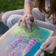 Stock Photo: Girl draws flowers with pastels