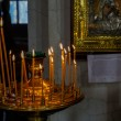 Interior of russian orthodox church. Candles under the ancient icon framed with the gold. - Stock Photo