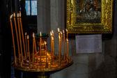 Interieur van de russisch-orthodoxe kerk. kaarsen onder het oude pictogram omlijst met het goud. — Stockfoto