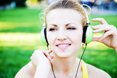 Young cheerful woman enjoing the music outdoors — 图库照片