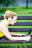 Lovely woman having rest in the park with laptop — Stock Photo