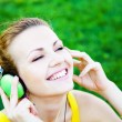 Young cheerful woman enjoing the music outdoors — Stock Photo