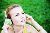 Young woman listening misic in the park — Stock Photo