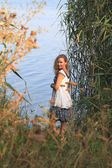 Girl on a background of the river with reeds — Stock Photo