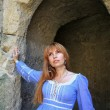 Stock Photo: Red-haired girl in blue dress near fortress wall