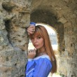 Red-haired girl in blue dress near fortress wall — Foto de stock #35846397
