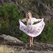 Blonde girl in a sundress barefoot on the stones — ストック写真