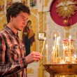 Young man lighting a candle in the church. — Stock Photo #13536698