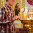 Stock Photo: Young man lighting a candle in the church.