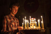 Young man lighting a candle in the church. — Stock Photo