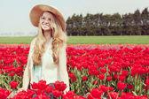 Woman in a red tulip field — Stok fotoğraf