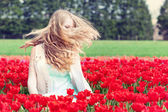 Woman in a red tulip field — Stock Photo