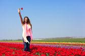 Mulher no campo de tulipa vermelha — Foto Stock