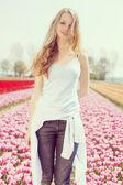 Woman in pink tulip field — Stok fotoğraf
